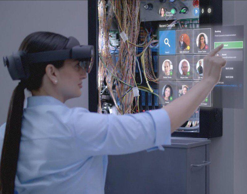 Una mujer interactuando con los hologramas de Hololens 2